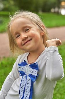 Portret uśmiechniętego dziecka na tle parku