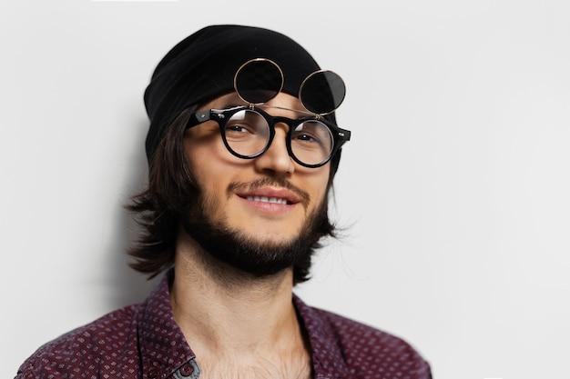 Portret uśmiechniętego faceta. nosi okrągłe okulary i kapelusz.