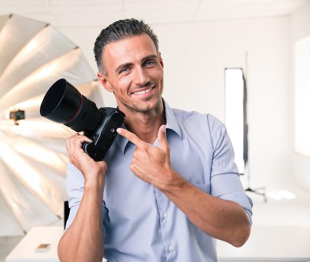 Portret uśmiechniętego fotografa wskazującego palcem na aparat w studio