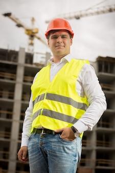 Portret uśmiechniętego inżyniera budowlanego w kasku