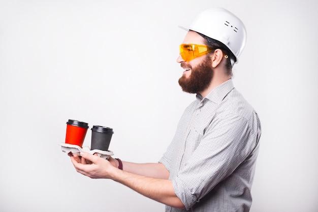 Portret uśmiechniętego inżyniera w białym kasku i rozdającego kawę na wynos pracownikom lub współpracownikom