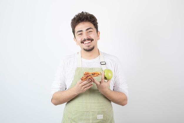 Portret uśmiechniętego kucharza trzymającego jabłko i pizzę na białym tle
