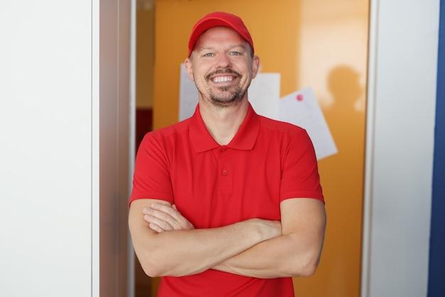 Portret uśmiechniętego kuriera w czerwonym mundurze