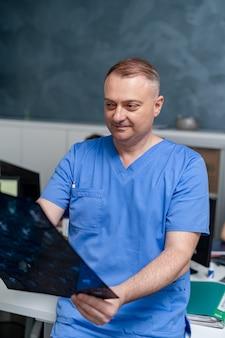 Portret uśmiechniętego lekarza. mężczyzna specjalista medyczny. chirurg lub radiolog na tle sali medycznej.