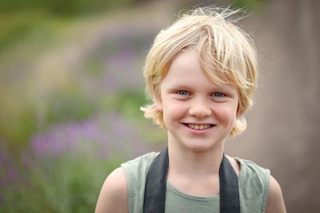 Portret uśmiechniętego małego kaukaskiego chłopca o blond włosach