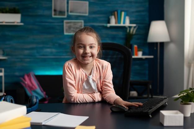 Portret uśmiechniętego małego ucznia siedzącego przy biurku w salonie