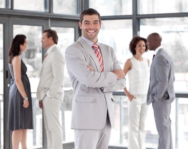 Portret uśmiechniętego menedżera prowadzącego jego zespół