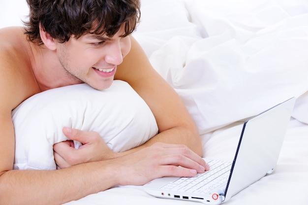 Portret uśmiechniętego mężczyzny leżącego na łóżku z laptopem