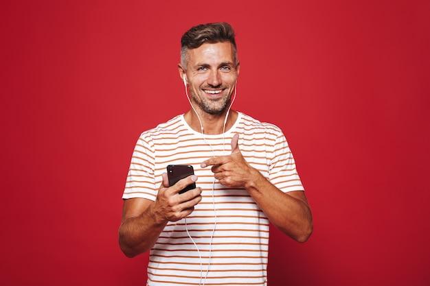 Portret uśmiechniętego mężczyzny stojącego na czerwono