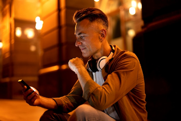 Portret uśmiechniętego mężczyzny w mieście w nocy ze słuchawkami i smartfonem
