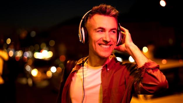 Portret uśmiechniętego mężczyzny w mieście w nocy ze słuchawkami