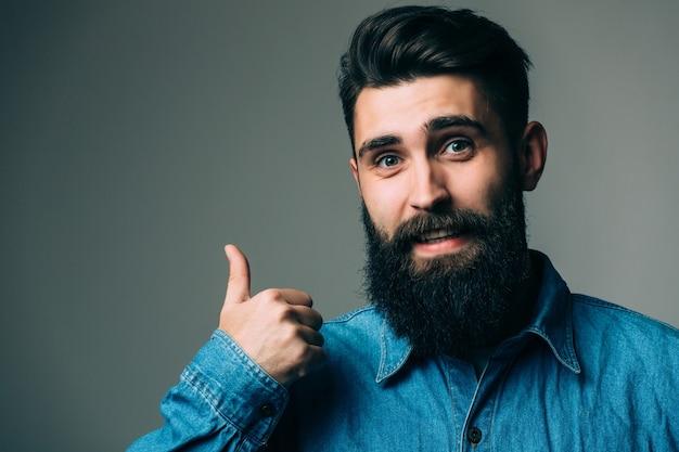 Portret uśmiechniętego mężczyzny w okularach pokazano kciuk na szarej ścianie