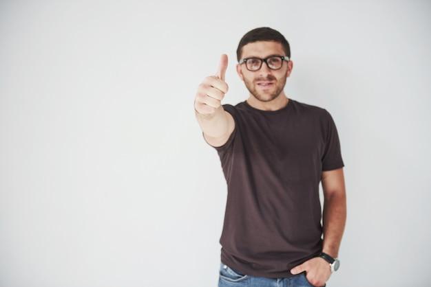 Portret uśmiechniętego mężczyzny w okularach pokazując kciuk nad białym
