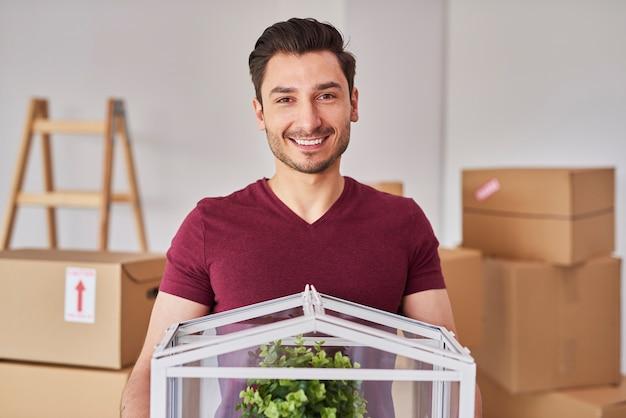 Portret uśmiechniętego mężczyzny wprowadzającego się do swojego nowego mieszkania