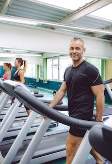Portret uśmiechniętego mężczyzny ze słuchawkami ćwiczącymi na bieżni w centrum fitness