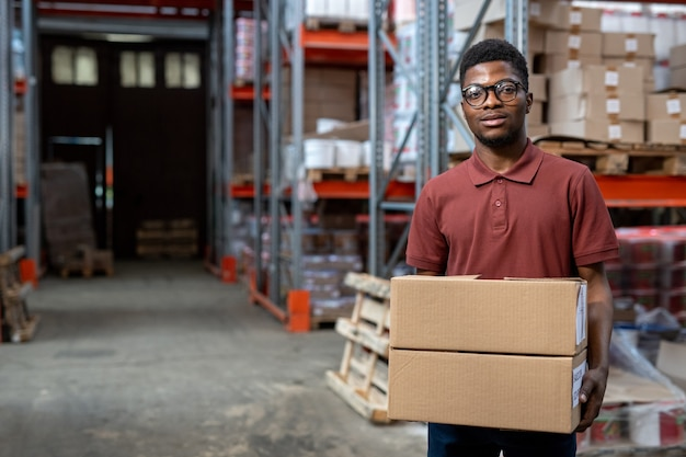 Portret uśmiechniętego młodego afroamerykańskiego pracownika magazynu w okularach, stojącego ze stosem pudeł w magazynie z metalową ramą