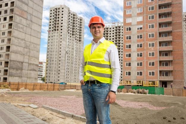 Portret uśmiechniętego młodego architekta stojącego przy budynkach w budowie