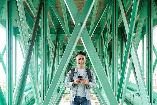 Portret uśmiechniętego młodego azjatyckiego mężczyzny z plecakiem stojącym z nowoczesnym telefonem między metalowymi dźwigarami mostu