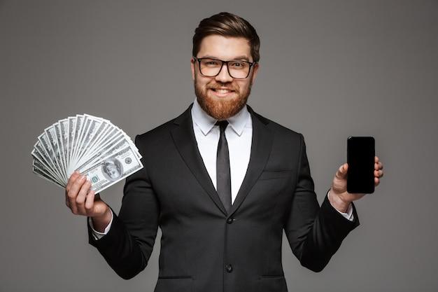 Portret uśmiechniętego młodego biznesmena ubranego w garnitur