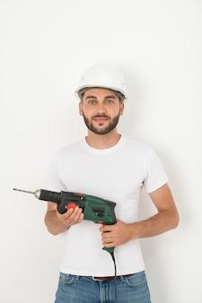 Portret uśmiechniętego młodego brodatego mechanika w kasku trzymającym bezprzewodowy śrubokręt i wiertło na białej ścianie