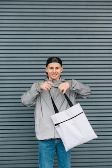 Portret uśmiechniętego młodego człowieka w modnej streetwear i czapce z eko torbą wielokrotnego użytku w ręku i patrząc w kamerę
