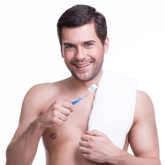Portret uśmiechniętego młodego człowieka ze szczoteczką do zębów - na białym tle.