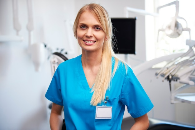 Portret uśmiechniętego, młodego dentysty w gabinecie stomatologicznym