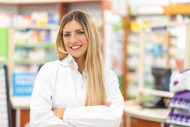Portret uśmiechniętego młodego farmaceuty w aptece
