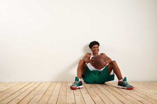 Portret uśmiechniętego młodego gracza siedzącego na drewnianej podłodze przy białej ścianie, trzymającego starą brązową piłkę do koszykówki
