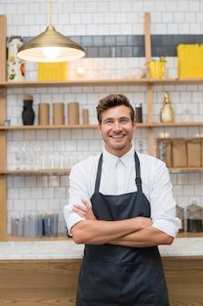 Portret uśmiechniętego młodego kelnera pochylonego przy kontuarze kawiarni z rękami skrzyżowanymi