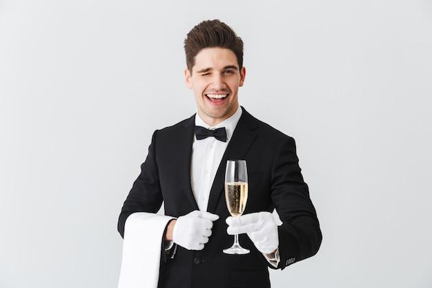 Portret uśmiechniętego młodego kelnera w smokingu proponuje kieliszek szampana na białej ścianie