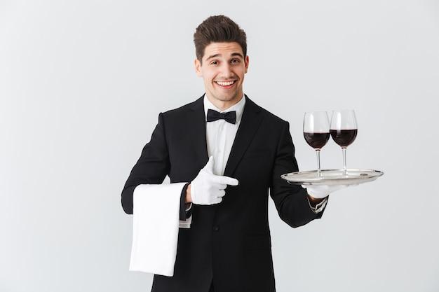 Portret uśmiechniętego młodego kelnera w smokingu, trzymając tacę z dwoma kieliszkami czerwonego wina na białej ścianie
