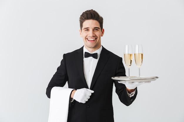 Portret uśmiechniętego młodego kelnera w smokingu, trzymając tacę z dwoma kieliszkami szampana na białej ścianie