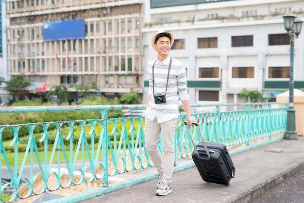 Portret uśmiechniętego młodego mężczyzny podróżującego z walizką