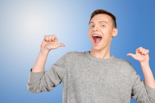 Portret uśmiechniętego młodego mężczyzny wskazującego na siebie