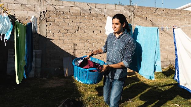 Portret uśmiechniętego młodego mężczyzny wywieszającego ubrania do wyschnięcia na podwórku