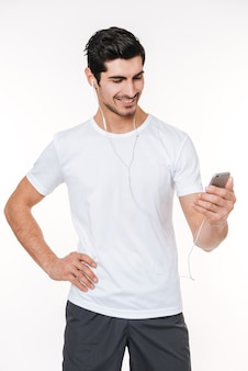 Portret uśmiechniętego młodego sportowca męskiego słuchającego muzyki za pomocą słuchawek i telefonu komórkowego na białym tle