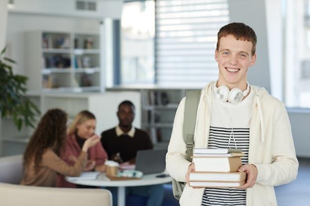 Portret uśmiechniętego nastolatka stojącego w bibliotece uczelni z ludźmi pracującymi w tle w pasie,