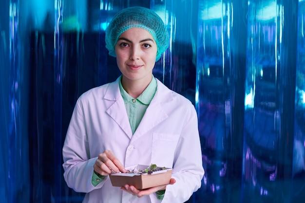 Portret uśmiechniętego naukowca trzymającego pudełko z zielonymi roślinami, podczas gdy pozuje przed niebieską plastikową ścianą, miejsce