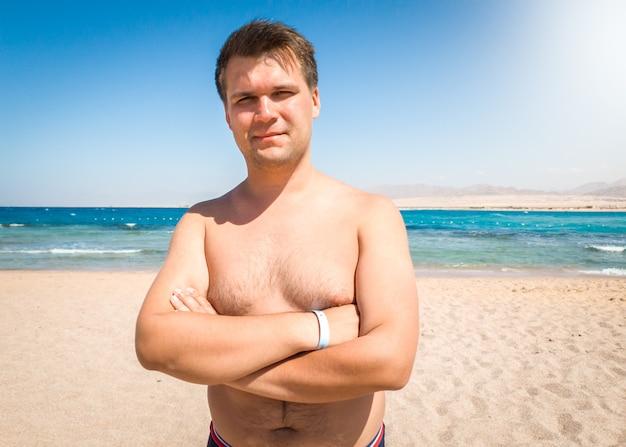 Portret uśmiechniętego otyłego mężczyzny z nadwagą pozowanie na plaży nad morzem i patrząc w kamerę