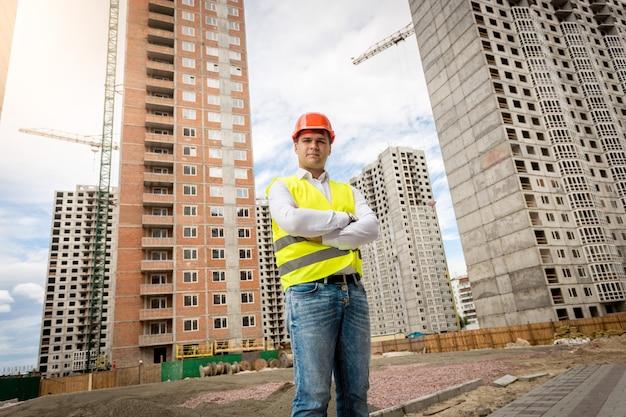 Portret uśmiechniętego pewnego siebie architekta stojącego przy budynkach w budowie