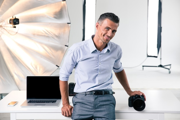 Portret uśmiechniętego, pewnego siebie fotografa opartego na stole w studio