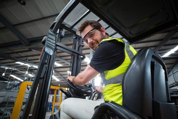 Portret uśmiechniętego pracownika fabrycznego napędowy wózek widłowy