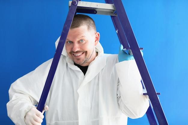 Portret uśmiechniętego pracownika płci męskiej w białym garniturze z drabiną