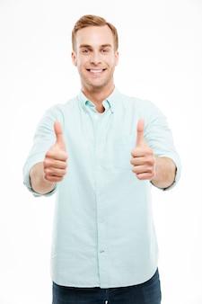 Portret uśmiechniętego przypadkowego mężczyzny pokazującego dwa kciuki w górę i patrzącego na przód nad białą ścianą