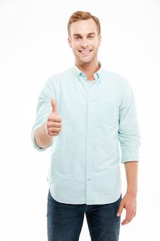 Portret uśmiechniętego przypadkowego mężczyzny pokazującego kciuk w górę i patrzącego na przód nad białą ścianą