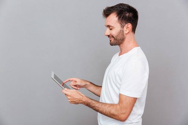 Portret uśmiechniętego przypadkowego mężczyzny trzymającego komputer typu tablet na szarym tle
