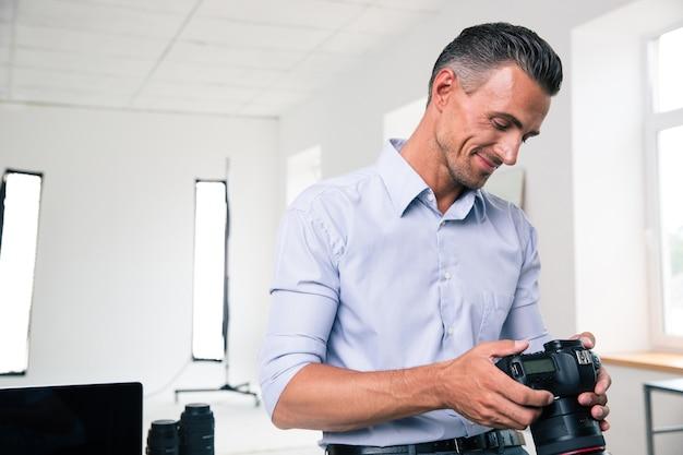 Portret uśmiechniętego przystojnego biznesmena używającego aparatu w studio