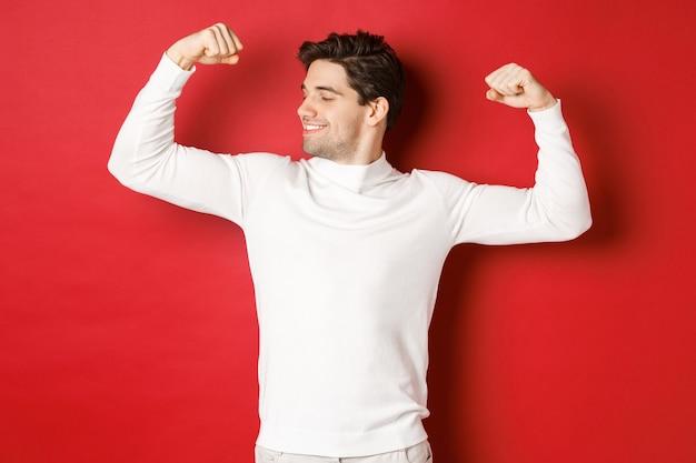 Portret uśmiechniętego przystojnego mężczyzny w białym swetrze napinającym bicepsy i chwalącym się pokazem siły ...