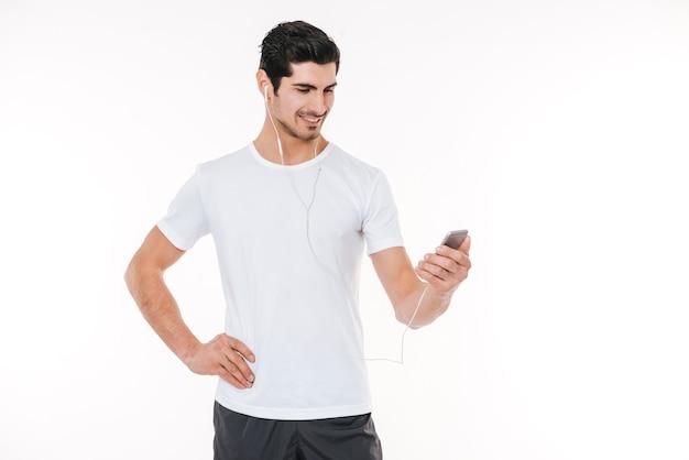 Portret uśmiechniętego przystojnego sportowca za pomocą telefonu komórkowego na białym tle